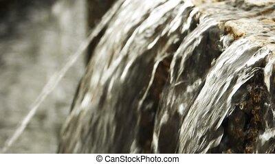 Artificial waterfall in the garden slow motion closeup shot.