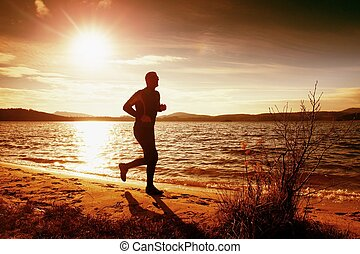 Silhouette of sport active man running and exercising on beach at busch below sunset.