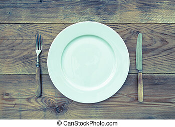 White plate with cutlery on wooden background