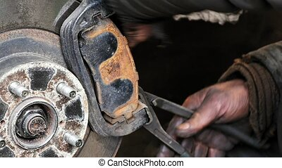 Auto mechanic working on brakes in car repair shop - Auto...
