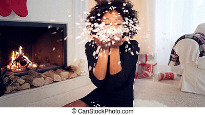 Young woman blowing Christmas confetti - Woman blowing white...