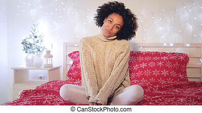 Smiling confident young woman sitting on her bed - Smiling...