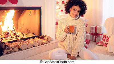 Happy young woman relaxing at Christmas with a mug of hot...