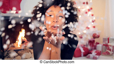 Young woman blowing confetti off her hands - Young african...