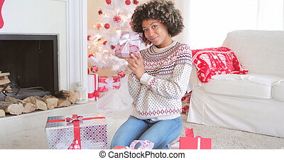 Pretty young woman checking her Christmas gifts - Pretty...