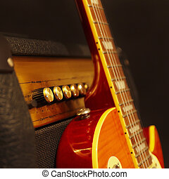 Electric guitar with amplifier on black background. Shallow...