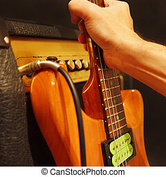 Hand puts electric guitar to combo amplifier on black...