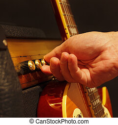 Hand adjusts combo amplifier for guitar with electric guitar...