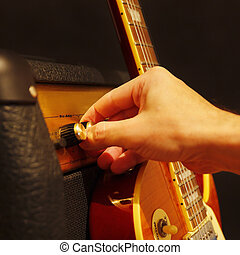 Hand adjusts amplifier for guitar with electric guitar on...