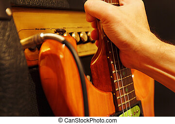 Hand takes electric guitar leaning against combo amplifier...