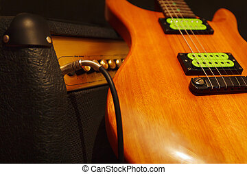 Mahogany electric guitar with combo amplifier on black...
