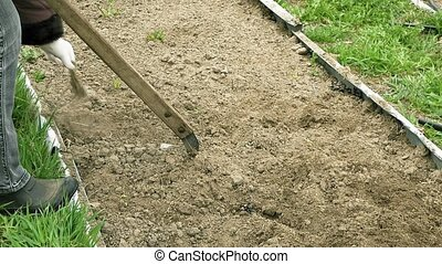 Country girl ploughs plows a bed vegetable garden - Country...