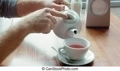 Man pours tea from teapot spills and wipes table - Man pours...