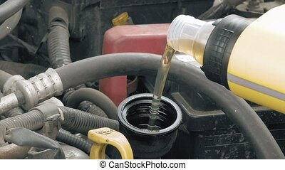 Auto mechanic pours additional motor engine oil into the...