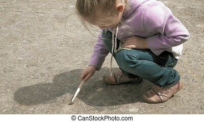 Little girl plays with bug beetle on the road - Pretty blond...