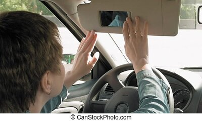 Woman corrects make-up in a car sun visor mirror - Pretty...