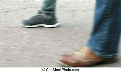 Women's feet on the sidewalk in shoes and sneakers trainers...