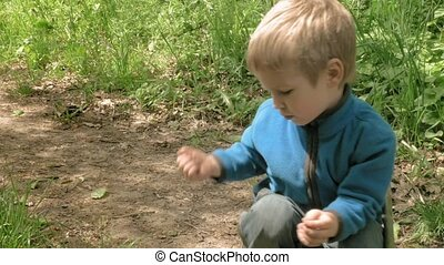 Little boy plays with flower in forest and smiles - Happy...