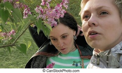 Two girls sniffing lilac flowers in the green park - Two...