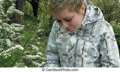 Pretty blond girl looks at flowers in a green park