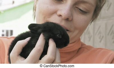 Girl holds and pets little baby black rabbit - Girl holds...