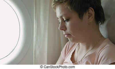 Airplane passenger scrolling through smart phone - A female...