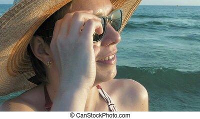 Woman in bikini straw hat putting off sunglasses - Woman in...