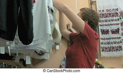 A customer trying to find perfect blouse in store - A...