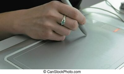 A woman draws with pen tablet digitizer and stylus - A woman...