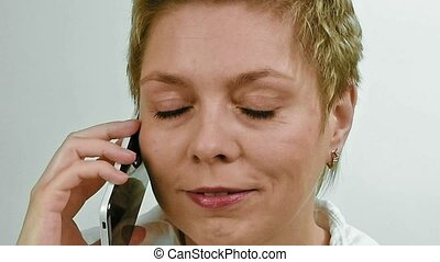 Excited blond woman emotionally talking by phone