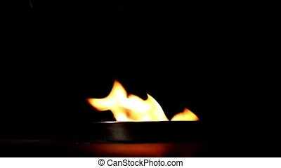 Flame rising in the darkness from metal dish