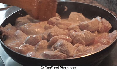Close up of a chicken meat cooking in the frying pan. -...