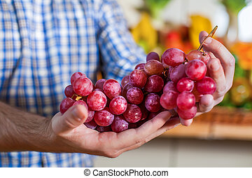 Man showing a bunch of grapes.