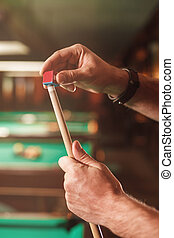 The male hands wipes a cue with chalk. Billiard tables on...