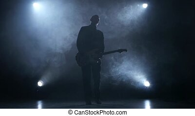 Electric guitar. The man plays for fun. Smoke. Slow motion -...
