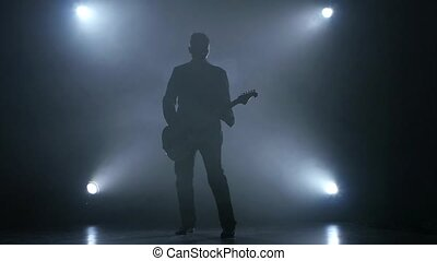 Guitarist plays electric guitar. Smoke background. Studio....