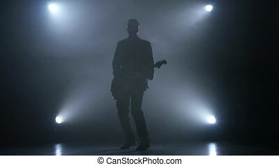 Concert musician electric guitar in smoke. Studio. Slow motion