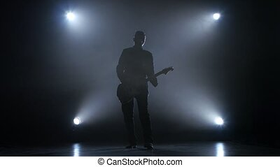 Guitarist in a dark studio plays a fast melody, performs a...
