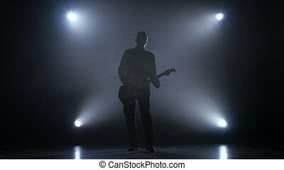Guitarist in a dark studio plays a fast melody