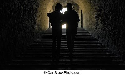 Silhouette of women going away in a dark tunnel - Silhouette...