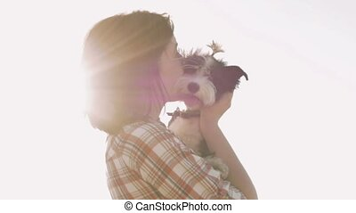 Woman holding dog in hands with backlight sunset - Young...