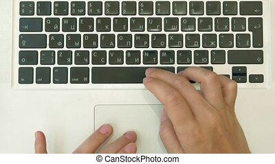 A person is typing on his laptop. Top view POV.