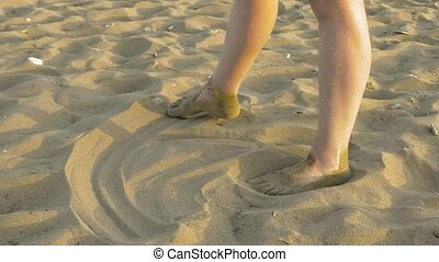 Woman is making imprints on the sand with her feet - A...