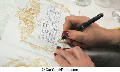 Woman writing greeting in the book of greetings at the...