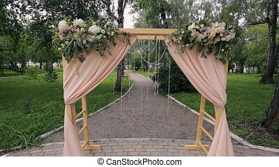 Wooden arch with curtains for ceremony on wedding day outdoors