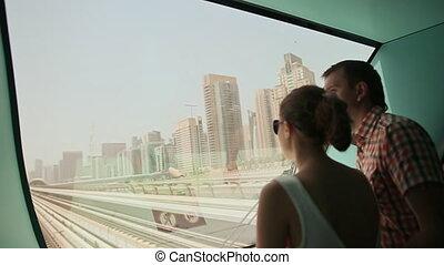 Love couple ride on a train Dubai Metro in a summer day 1