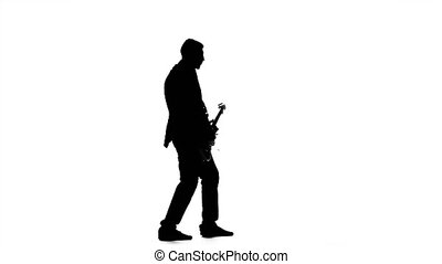 Guitarist plays fast melody on electric guitar. Silhouette. Studio