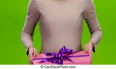 Girl holding out a box with a gift. Close up - Girl holding...