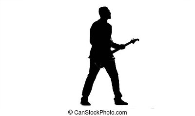 Guitarist plays bass guitar. Silhouette. Studio - Guitarist...