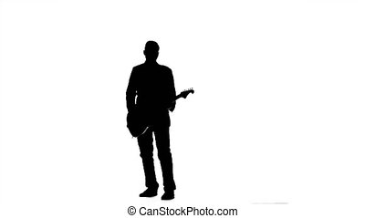Guitarist jumps up and pluck the strings while playing. Silhouette